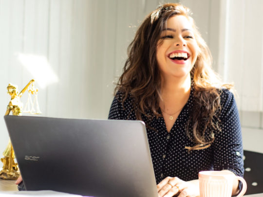 Woman on laptop smiling creating Amazing WordPress Pages Easily